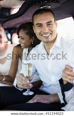 Well dressed man drinking champagne in a limousine - stock photo