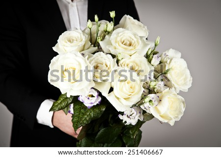 well-dressed man holding a bouquet of flowers. Holidays and celebrations. Wedding day. - stock photo