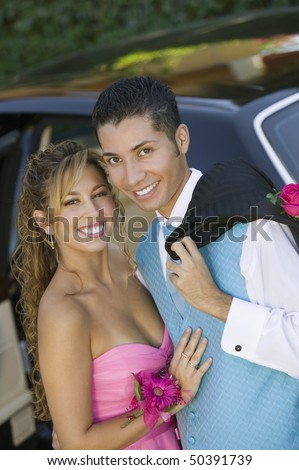 Well dressed teenage couple outside limo, portrait - stock photo