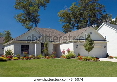 Well landscaped brick ranch with a vibrant blue sky background. Very colorful photo. - stock photo
