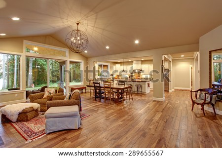 Well lit dinning room with connected living room with lots of decor. - stock photo