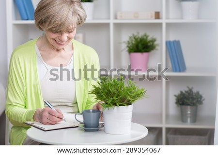 Well organized senior woman with notebook, horizontal - stock photo