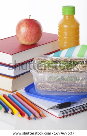 Well prepared school lunch with books and pencils on white isolated background - stock photo