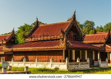 Well-preserved and/or reconstructed wooden buildings at the Mandalay Royal Palace compound seen at late afternoon sun - stock photo
