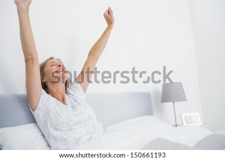 Well rested blonde woman stretching in bed and smiling in bedroom at home - stock photo