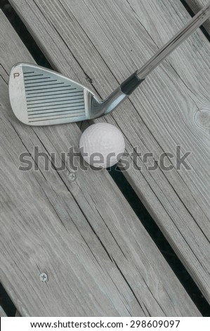 "Well-used golf club pitching wedge (marked ""P"") and golf ball on a weathered wooden deck. - stock photo"