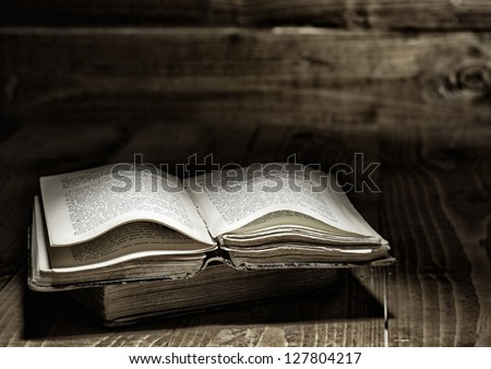 Well used open book on wooden table - stock photo