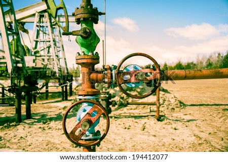 Wellhead with valve armature and pump jack. Extraction of oil. Toned. - stock photo