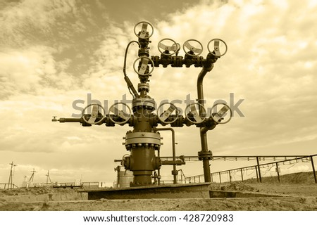 Wellheads and pipeline with valves. Oil and gas theme. Toned sepia. - stock photo
