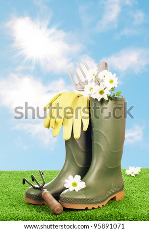 Wellington boots with garden tools on grass with blue summer sky - stock photo