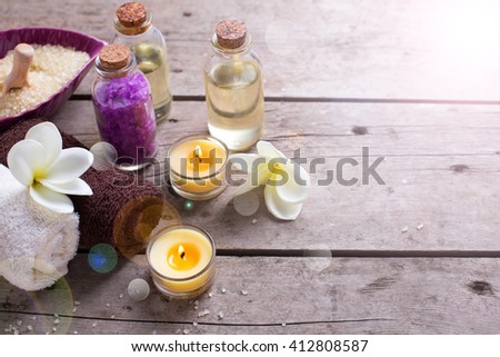 Wellness or spa  setting. Bottles with aroma oil, sea salt, towels  and  white  plumeria flowers in ray of light on vintage wooden background. Selective focus. Place for text. - stock photo