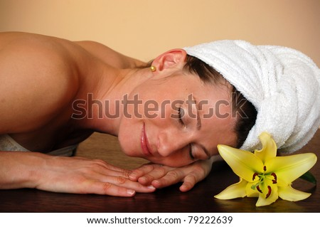 Wellness - Pretty woman with flower relaxing in spa - stock photo