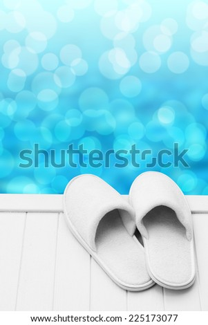 Wellness slippers on pier with bokeh background  - stock photo