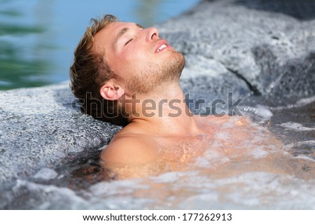 Wellness Spa - man relaxing in hot tub whirlpool Jacuzzi outdoor at luxury resort spa retreat. Handsome young male model relaxed with eyes closed resting in water near pool on travel vacation holiday. - stock photo
