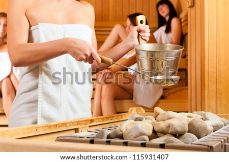 Wellness - young happy women in sauna of a Spa, water and scent are splashed on hot stones for steam - stock photo
