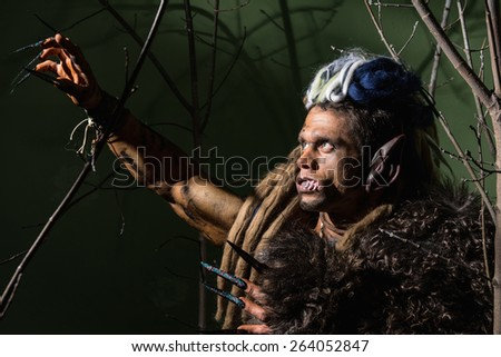 Werewolf with long nails and crooked teeth among the branches of the tree. - stock photo