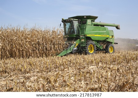 WEST ALBANY, MINNESOTA, USA - October 12, 2010: A farmer harvests corn in a John Deere combine. John Deere is a major manufacturer of agricultural machinery.  - stock photo