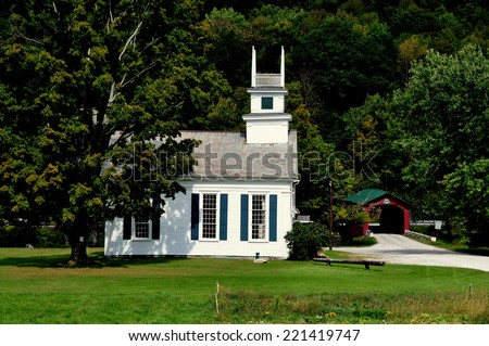 West Arlington, Vermont:  The United Methodist Church on the Green and 1852 covered bridge over the Battenkill River - stock photo