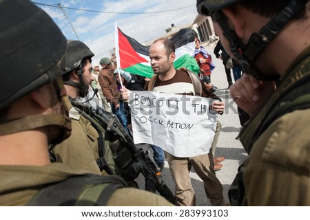"WEST BANK, OCCUPIED PALESTINIAN TERRITORIES - NOVEMBER 9: A Palestinian with a sign, ""Boycott the Occupation"", faces Israeli soldiers in a protest in Al Ma'sara, West Bank, November 9, 2012. - stock photo"