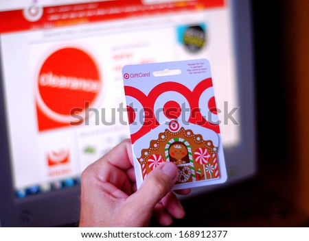 WEST PALM BEACH, FL - DECEMBER 28, 2013: A  man's hand is holding a Target gift card, getting ready to use it for on line purchases during after Christmas shopping at a clearance sale. - stock photo