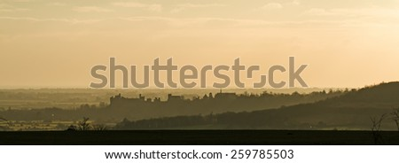 West Sussex country town of Arundel at sunset, with Arundel Castle and Arundel Cathedral silhouetted and the English Channel beyond. - stock photo