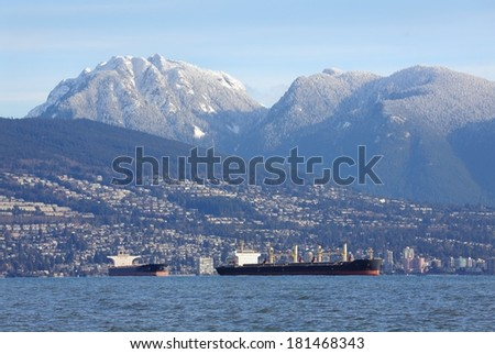 West Vancouver, Coast Mountains, Freighters. Freighters anchored in front of the West Vancouver shoreline of English Bay. The Coast Mountains rise in the background. British Columbia, Canada.  - stock photo