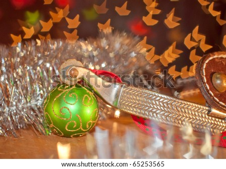 Western cowboy Christmas - spur and a green ball ornament on silver tinsel with starry light background - stock photo