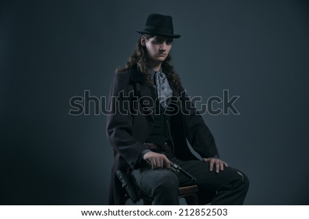 Western 1900 fashion man with brown hair and hat sitting on chair holding gun. Studio shot against grey. - stock photo