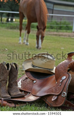 Western Gear with horse grazing in background - stock photo