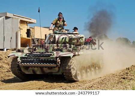 WESTERNHANGER, UK - JULY 18: A replica Panzer III tank speeds around the arena during one of the major WW2 battle reenactments for the public to view at the W&P show on July 18, 2014 in Westernhanger  - stock photo