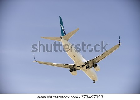 WESTJET AIRLINES - MAY 31, 2014: Boeing 737-800 with two jet engines is photographed before landing in Vancouver, YVR. The owner, Canadian compay WestJet Airlines was founded in 1996. British Columbia - stock photo