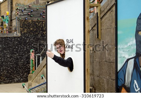 WESTON-SUPER-MARE, UK - AUGUST 26, 2015:  A visitor makes use of the selfie-hole parody at Dismaland in Weston-Super-Mare Somerset.  The resort has become very popular thanks to the work of Banksy. - stock photo