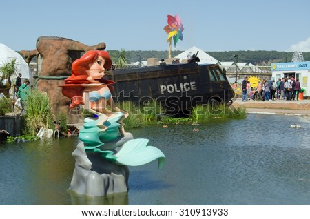 WESTON-SUPER-MARE, UK - AUGUST 26, 2015:  The Little Mermaid mutated by the toxic lake at Dismaland in Weston-Super-Mare.  The Banksy inspired parody fairground has attracted thousands of visitors. - stock photo