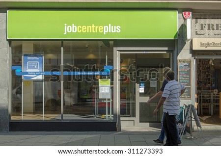 WESTON-SUPER-MARE, UK - AUGUST 26, 2015:  Two men walking past the Job Centre Plus government employment office in the centre of Weston-Super-Mare, Somerset on a sunny day in August. - stock photo