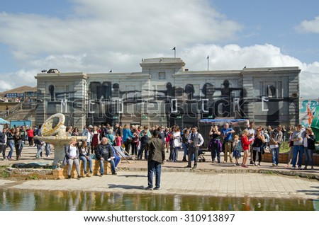 WESTON-SUPER-MARE, UK - AUGUST 26, 2015:  Visitors crowding the 'mediocre' Dismaland theme park inspired by Banksy and erected in a disused swimming pool in the Somerset resort of Weston-Super-Mare.  - stock photo