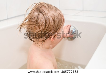Wet baby girl with blond hair looks at her reflection in overflow drain knob of the bathtub. - stock photo