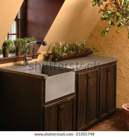 Wet bar by window, dark wood cabinets with slate sink and counter top. - stock photo