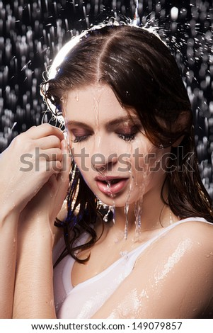 Wet beauty. Portrait of beautiful young women with closed eyes standing under the rain - stock photo