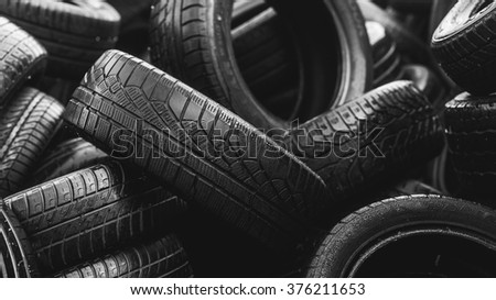 Wet black used car tires on each other in big stack  - stock photo
