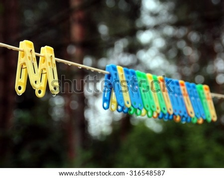 Wet bright multicolored clothespins on the clothesline after a rain. Colorful pegs with raindrops on the backyard background. Concept photo: when it's raining in the dryer day. - stock photo