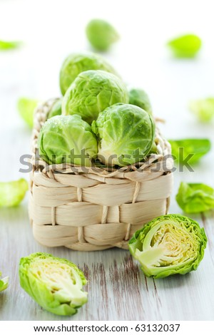 Wet brussels sprouts in basket on the white wooden table - stock photo