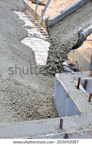 Wet cement pours down a concrete truck chute to fill a slab at a home building construction site.  - stock photo