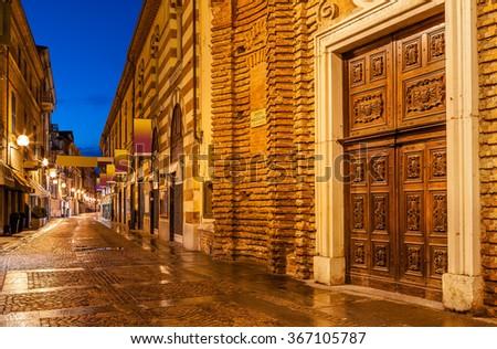 Wet cobbled pedestrian street in evening in Alba, Piedmont, Northern Italy. - stock photo