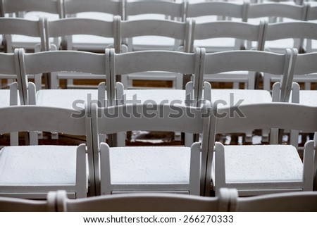 Wet empty chairs before an outdoor wedding ceremony - stock photo