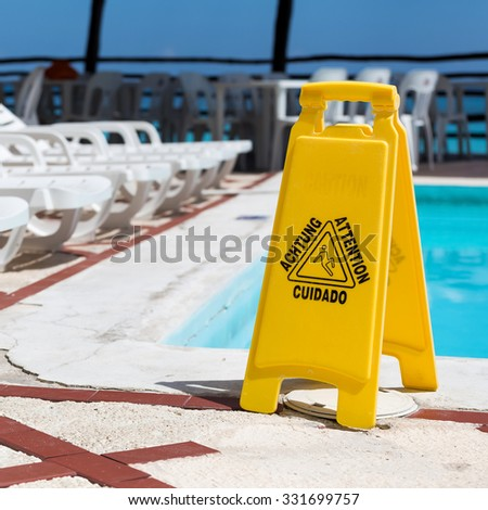 Wet floor warning sign near a swimming pool - stock photo