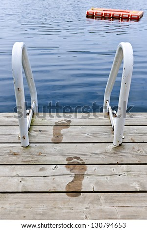 Wet footprints on dock with ladder and diving platform at calm summer lake in Ontario Canada - stock photo