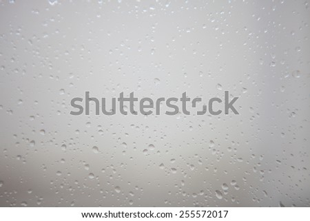 Wet glass with drops of rain fall on the street - stock photo