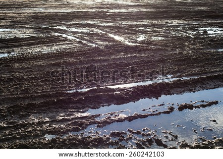 Wet ground surface after the rain with lots of wheel tracks - stock photo
