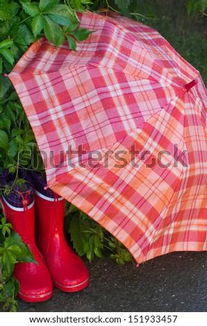 Wet gumboots and umbrella in garden - stock photo