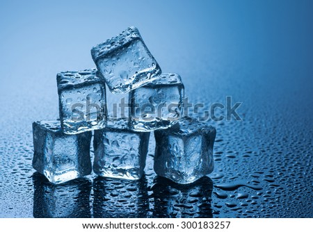 wet ice cubes on blue background with water drops .  - stock photo